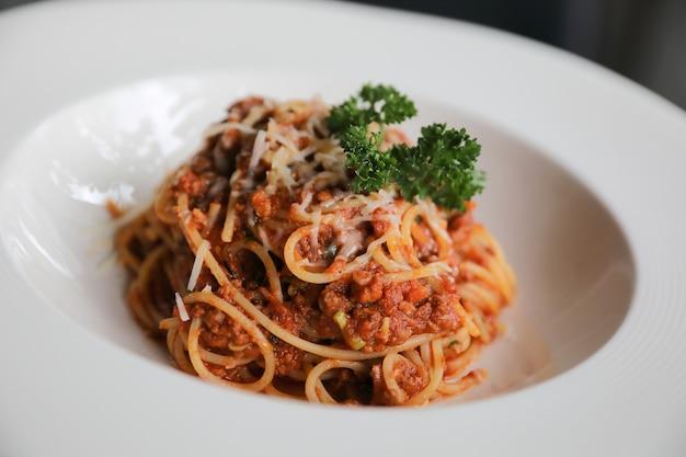 牛挽肉とトマトソースにパルメザンチーズとバジルを添えたスパゲッティボロネーゼ、イタリア料理