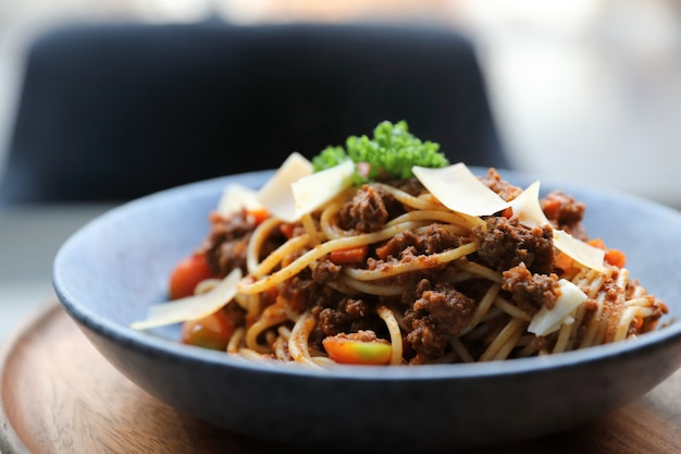 Spaghetti bolognese with minced beef and tomato sauce garnished with parmesan cheese and basil