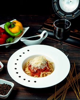 Spaghetti bolognese with red wine on the table