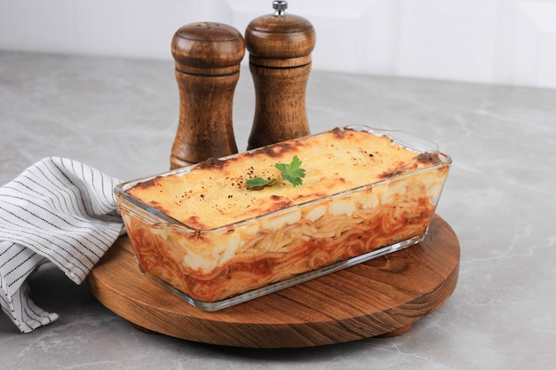 Spaghetti brulle on clear baking dish l with staiinless spoon and fork. spaghetti brulee is baked spaghetti with bechamel and bolognese sauce. copy space for text
