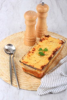 Spaghetti brulle on clear baking dish l with staiinless spoon and fork. spaghetti brulee is baked spaghetti with bechamel and bolognese sauce
