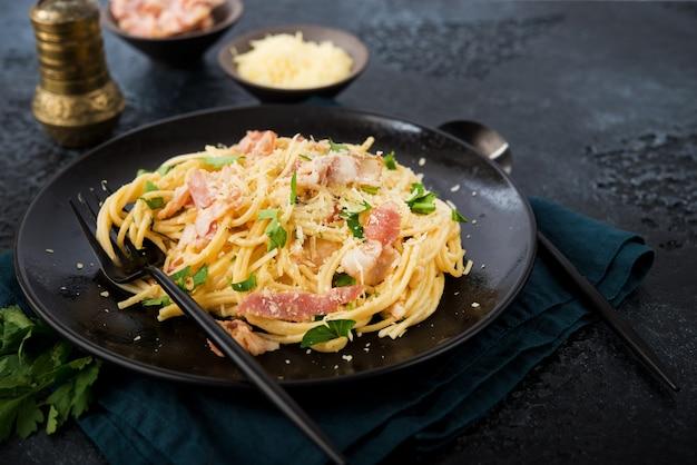 Спагетти карбонара с беконом и пармезаном на тарелке