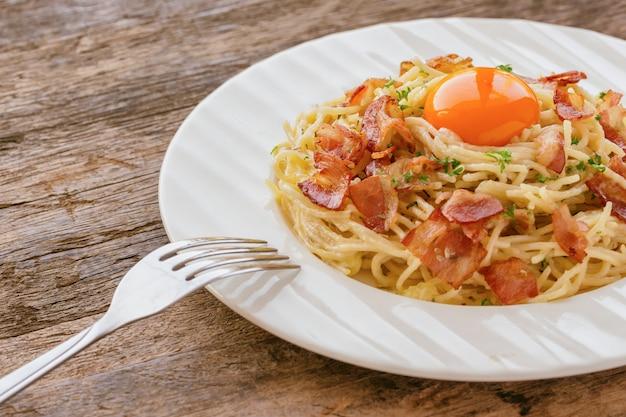 ベーコン、チーズ、卵黄、振りかけるパセリのスパゲティカルボナーラ
