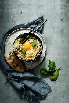 Spaghetti carbonara with cream sauce, bacon, yolk on a dark background. filing in asian style