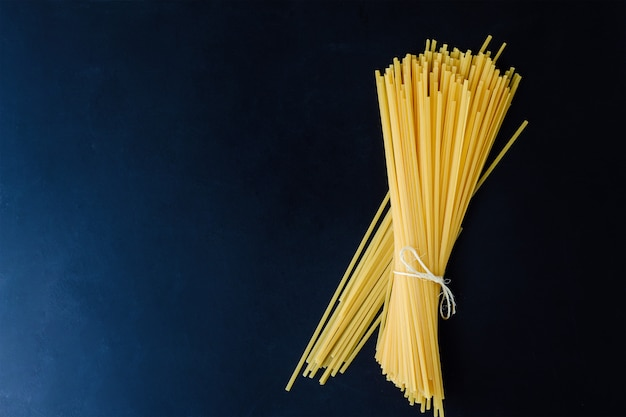 Spaghetti on a dark background, bandaged with ribbon