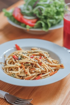 Spaghetti dish with wok vegetables and fresh salad in a restaurant. close-up.