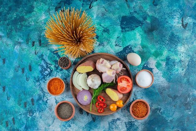 Ciotola di spaghetti, uova e spezie accanto a varie verdure e coscia di pollo su un piatto di legno, su sfondo blu.