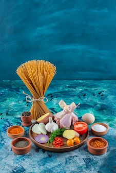 Spaghetti, egg and spice bowl beside various vegetables and chicken drumstick on a wooden plate on the blue surface