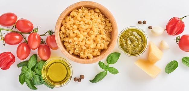 スパゲッティ、フレッシュトマト、ハーブ、スパイス。白い背景、上面図に分離された健康食品成分の組成。モックアップ。