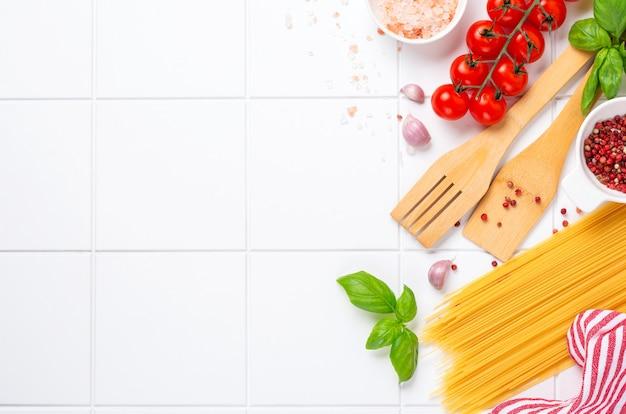 스파게티, 신선한 토마토, 허브 및 향신료. 흰색 배경, 평면도에 고립 된 건강 식품 재료의 구성. 모의.