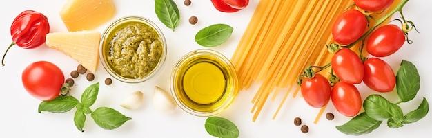 スパゲッティ、フレッシュトマト、ハーブ、スパイス。白い背景、上面図に分離された健康食品成分の組成