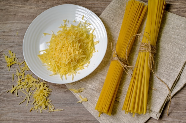 Spaghetti and grated cheese on white plate