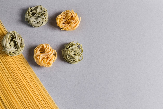 Spaghetti and green and yellow tagliatelle on light background