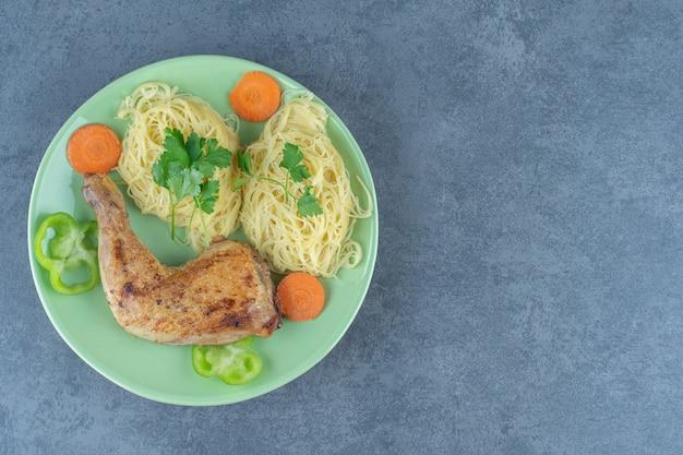 Spaghetti e gamba alla griglia su piatto verde.
