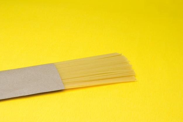 Спагетти в пакете из экологически чистой бумаги на желтом фоне