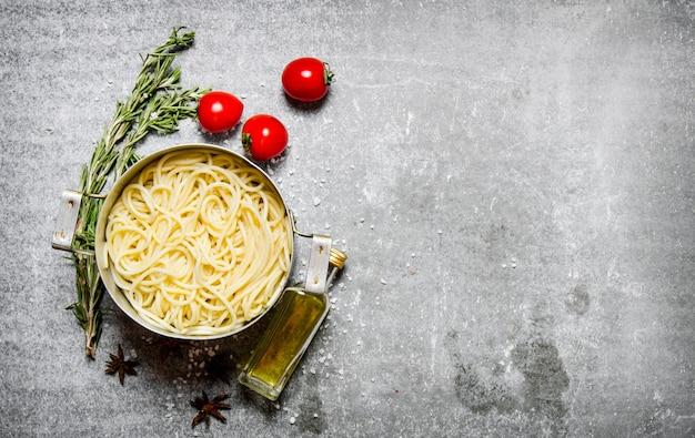 Спагетти на сковороде с помидорами, оливковым маслом и зеленью. на каменном столе. свободное место для текста. вид сверху