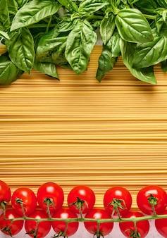 Итальянская паста спагетти с листьями базилика и помидорами черри, оформленными в цветах итальянской кухни.