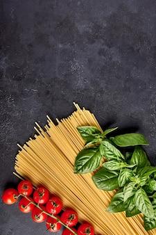 Итальянская паста спагетти с листьями базилика и помидорами на темном текстурированном фоне, расположенных в