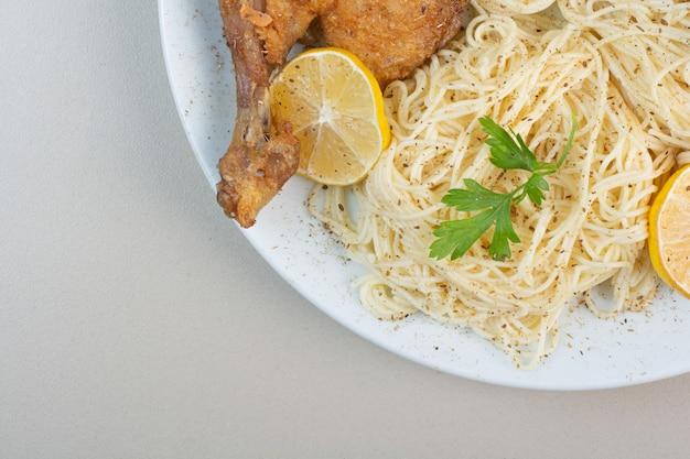 Спагетти, лимон и куриная ножка на белой тарелке