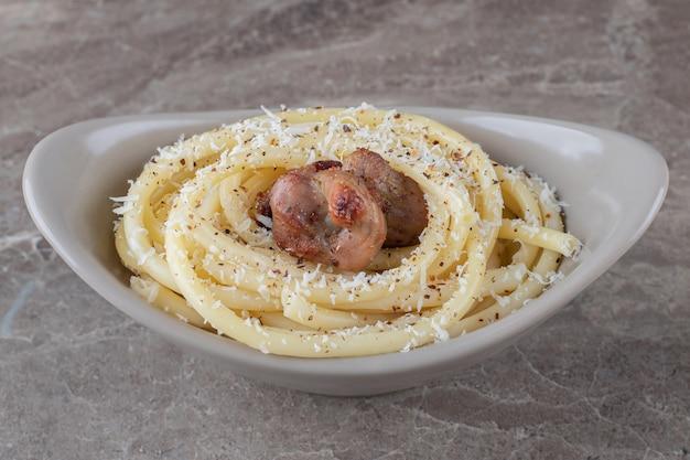 Spaghetti e carne sulla ciotola, sulla superficie di marmo.