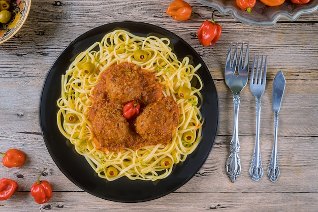 Spaghetti and meatballs with tomato sauce in black dish on wooden