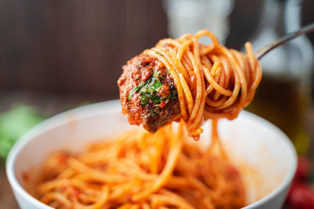 Spaghetti and meatballs with tomato sauce in white bowl on wooden rustic board