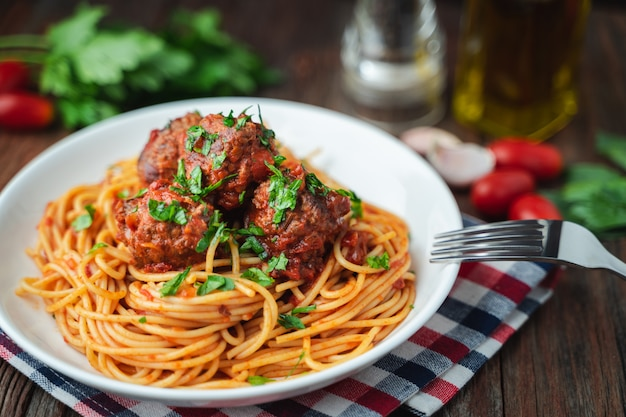 Spaghetti and meatballs with tomato sauce in white dish on wooden rustic board