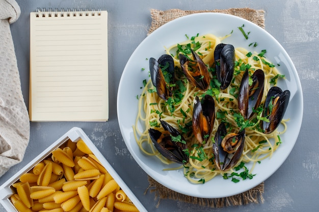 Spaghetti and mussel in a plate with copybook, raw pasta, kitchen towel