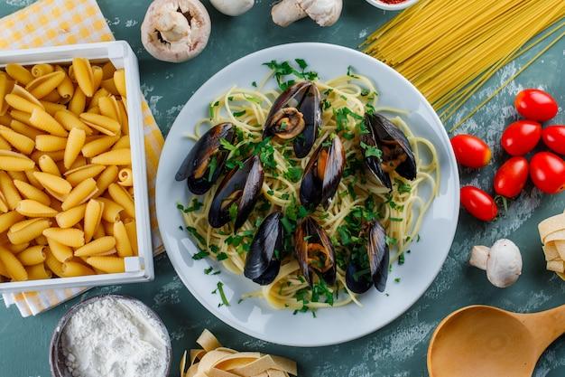 Spaghetti e cozze in un piatto con pasta cruda, pomodoro, farina, funghi, cucchiaio di legno