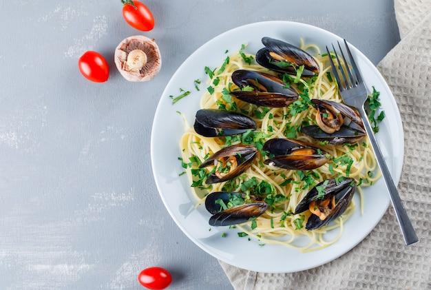 Spaghetti e cozze con pomodori, funghi, forchetta in un piatto sul telo da cucina