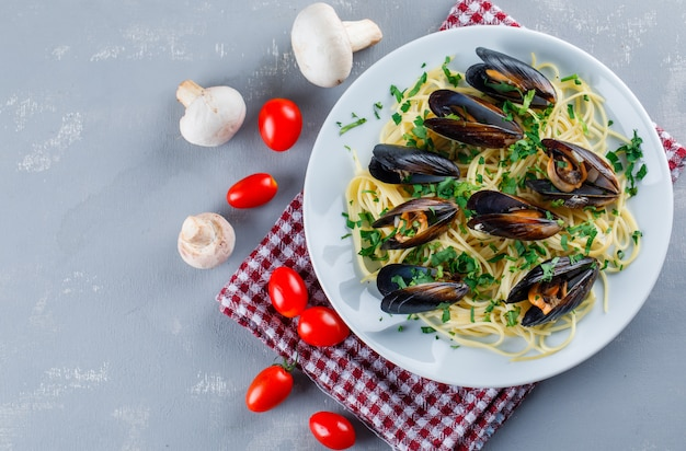 Spaghetti and mussel with tomatoes, mushrooms in a plate on plaster and kitchen towel