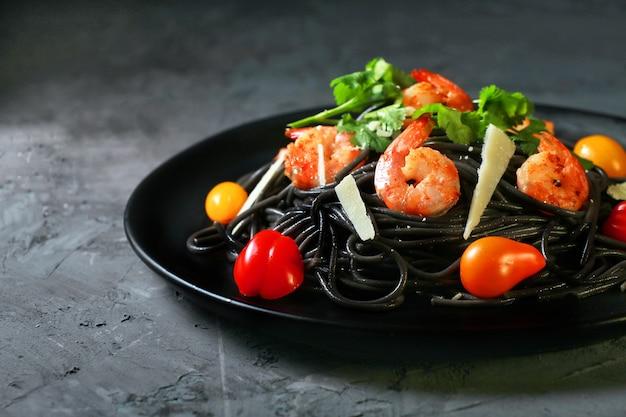 Спагетти негро, итальянская черная паста с морепродуктами, с креветками, сыром, помидорами, горизонтальная, черный фон