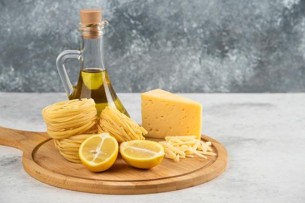 Гнезда спагетти, масло, лимонный сыр на деревянной доске.