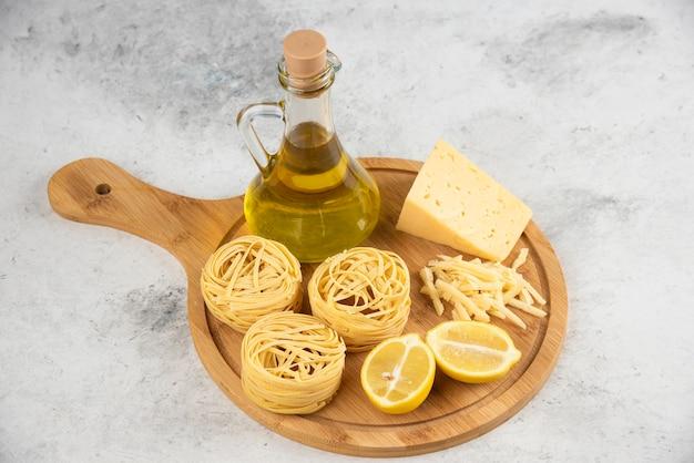 Spaghetti nests, oil, lemonnd cheese on wooden board.