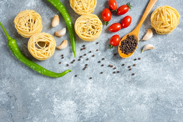 Nidi di spaghetti, peperoni e pomodori su fondo di marmo.