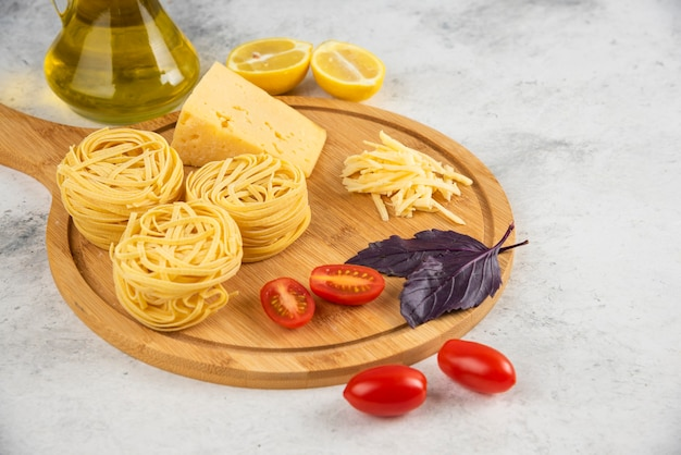 Spaghetti nests, vegetables and cheese on wooden board.