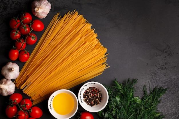 暗い背景のスパゲッティ。スパゲッティとチェリー。イタリアのパスタを野菜で調理する