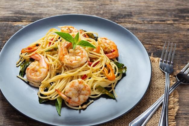Спагетти на черной тарелке на деревянном фоне.