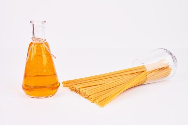オイルのボトルとガラスのコップからスパゲッティ。
