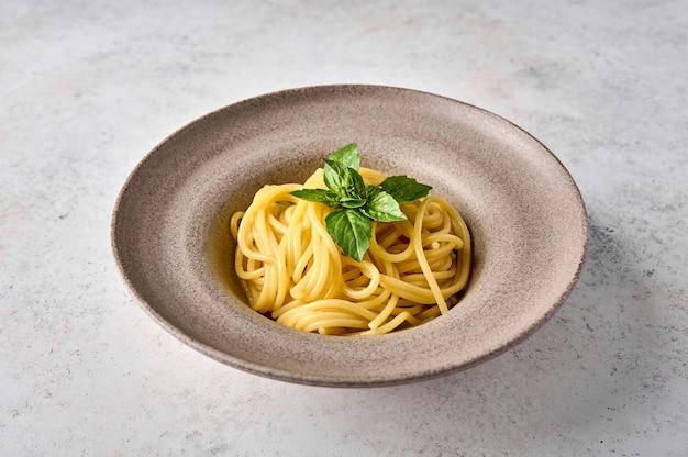Макароны спагетти и базилик на керамической тарелке на светлом фоне крупным планом