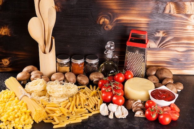 さまざまな新鮮な野菜やスパイスの横にあるスパゲッティ、パスタ、未調理のマカロニ