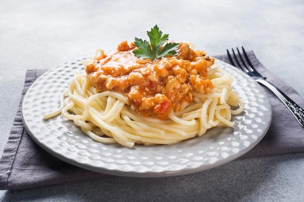 Spaghetti pasta bolognese on white plate, gray table