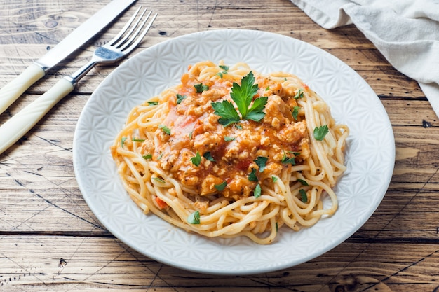 Spaghetti pasta bolognese on white plate, wooden table