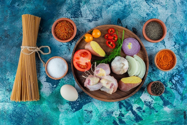 Spaghetti pasta, egg and spice bowl beside various vegetables and chicken drumstick on a wooden plate on the blue surface