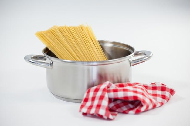 白い背景の上の道具のスパゲッティパスタ