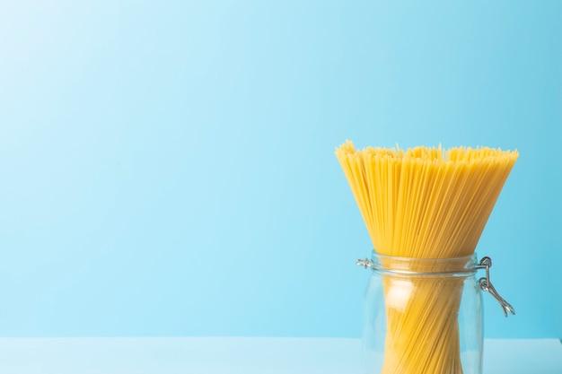 Макаронные изделия спагетти на пустой голубой предпосылке. сырые свежие изолированные спагетти в банке перед приготовлением итальянской еды.