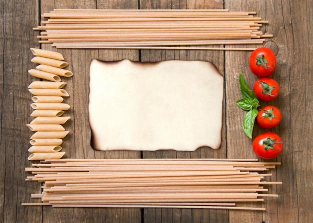 Макароны спагетти, помидоры и базилик кадр с бумагой на деревянном фоне вид сверху