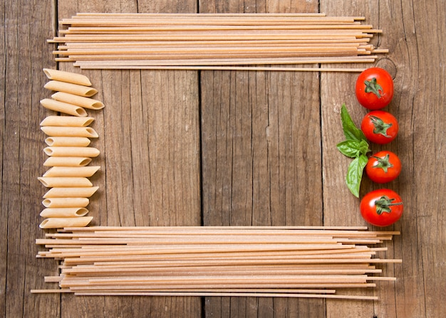 Spaghetti pasta, tomatoes and basil on wooden background top view
