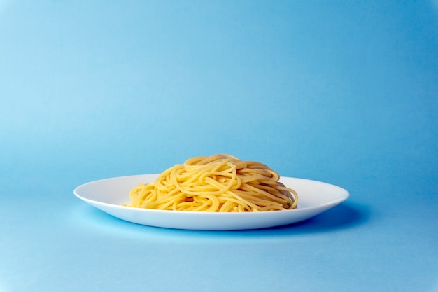 Spaghetti pasta on a white plate on a blue background