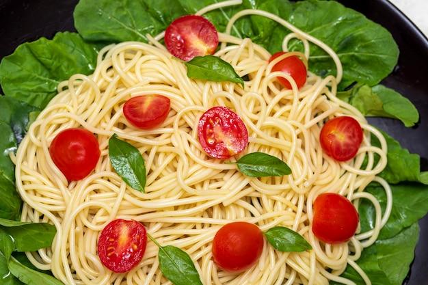 ルッコラとチェリートマトのスパゲッティパスタ Premium写真